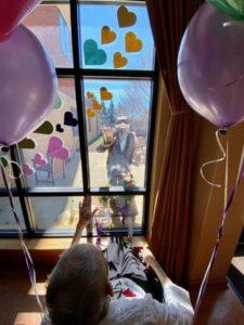 Couple celebrates wedding anniversary through a glass wall